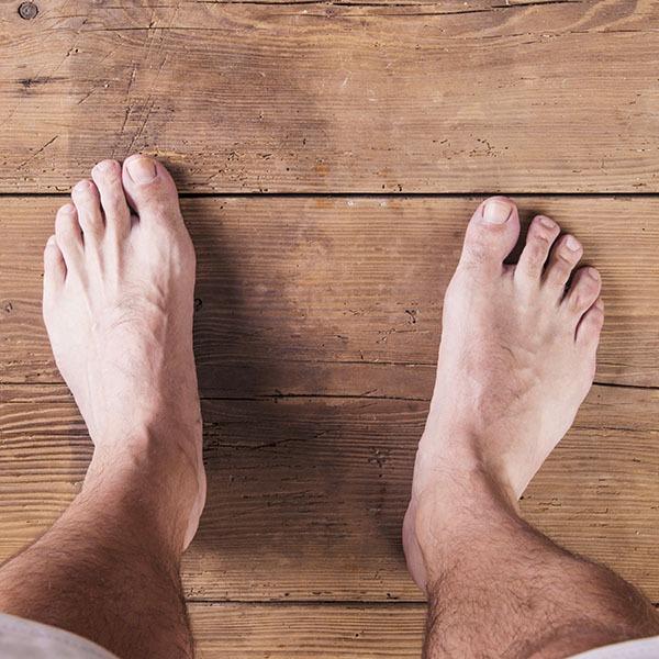Jalat ylhäältä kuvattuna puulankun päällä